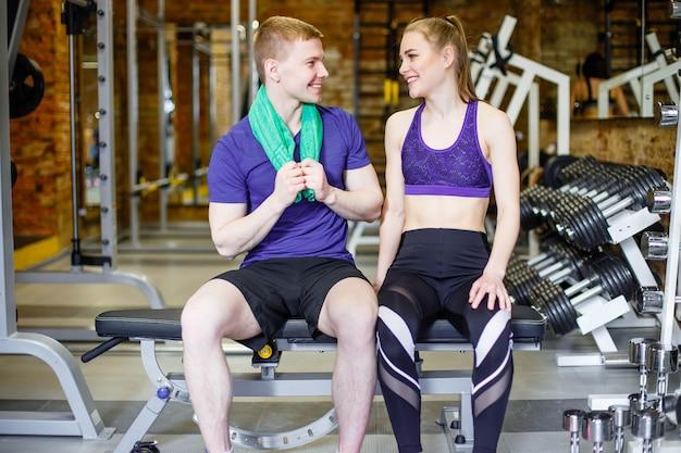 トレーニングの後休んでジムでスポーツウェアの若い男女