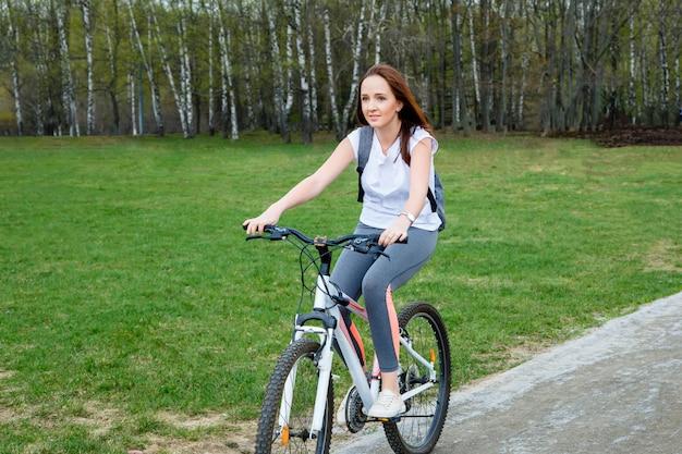 公園に乗って幸せな若い自転車の肖像画
