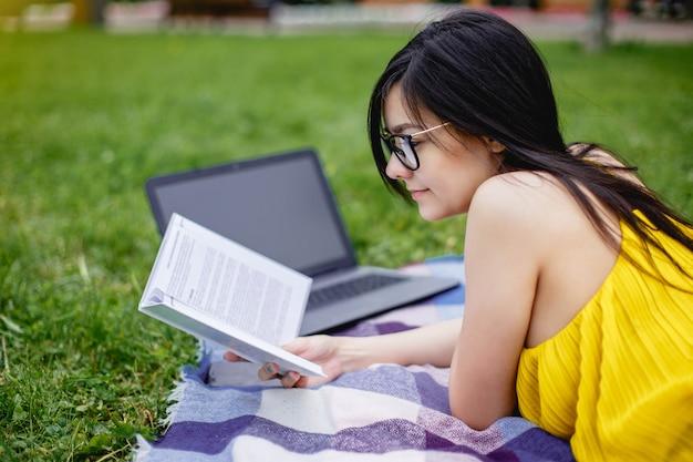 Красивая девушка студента прочитала книги и портативный компьютер на зеленой траве в парке в временени.
