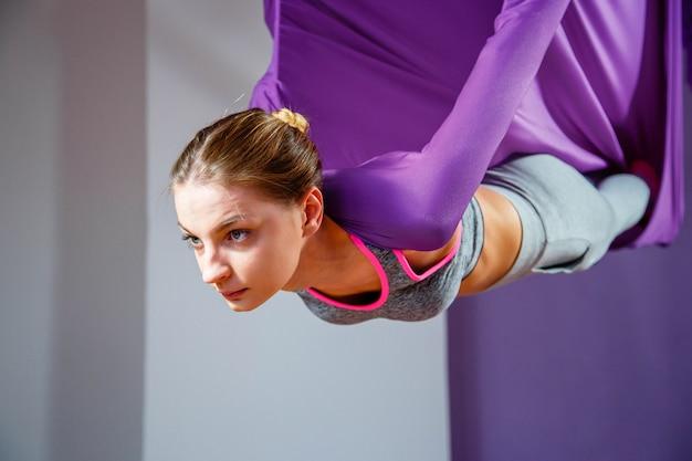 反重力ヨガを作る若い女性の肖像画。空中エアロフライフィットネストレーナートレーニング。