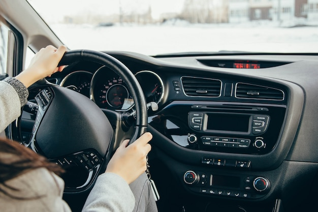 駆動輪に女性の手。現代の自動車のステアリングホイールと手のクローズアップを運転