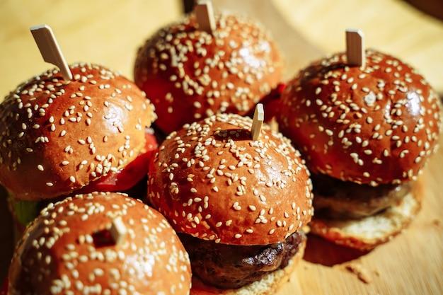 木製のテーブルに美味しいハンバーガーがたくさん