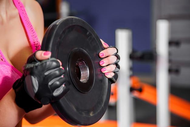 ジムでヘビー級バーベルプレートでのエクササイズ女性の手のクローズアップ。クロスフィットワークアウト