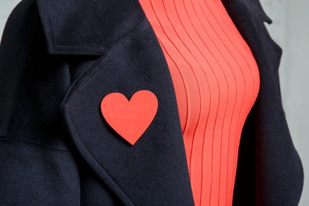 婦人服のディテール。黒いコートにハートの形のブローチ