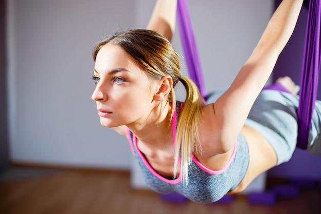 反重力ヨガを作る若い女性の肖像画。空中エアロフライフィットネストレーナートレーニング。調和と静けさの概念