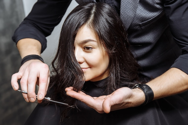 若い女性が理髪店で新しい散髪を取得します。