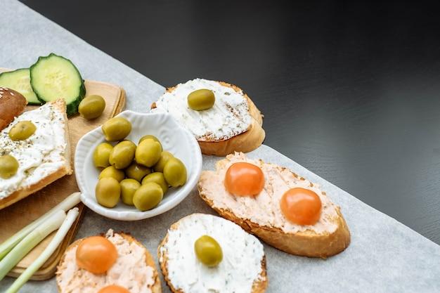 チェリートマト、きゅうり、グリーンオリーブ、クリームチーズと無愛想なバゲットのスライスの平面図です。