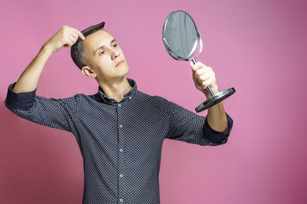 若い男がピンクの背景に鏡の前で彼の髪をとかす。