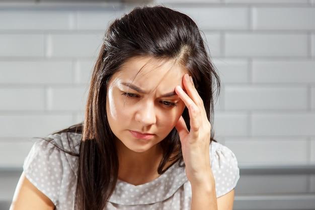 頭を抱えている頭痛を持つ若い女性。頭痛、女性、感情的ストレス