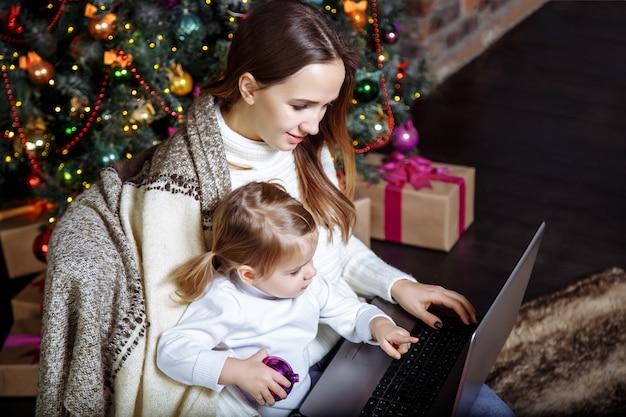 Мать показывает ребенку что-то в ноутбуке возле елки