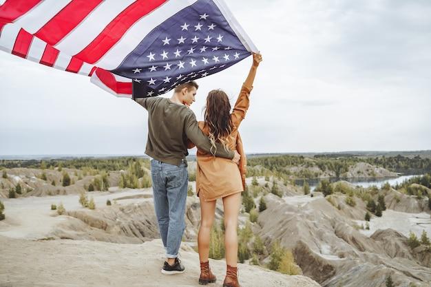 自然の中で手を振っているアメリカの国旗を保持している幸せな若いカップル