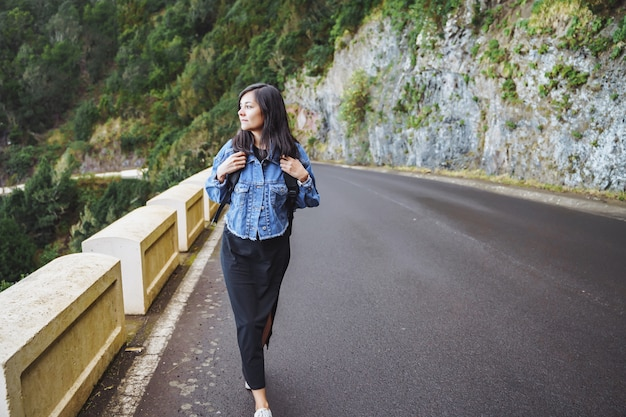 Путешественник женщина с рюкзаком, наслаждаясь и ходить по дороге в горах