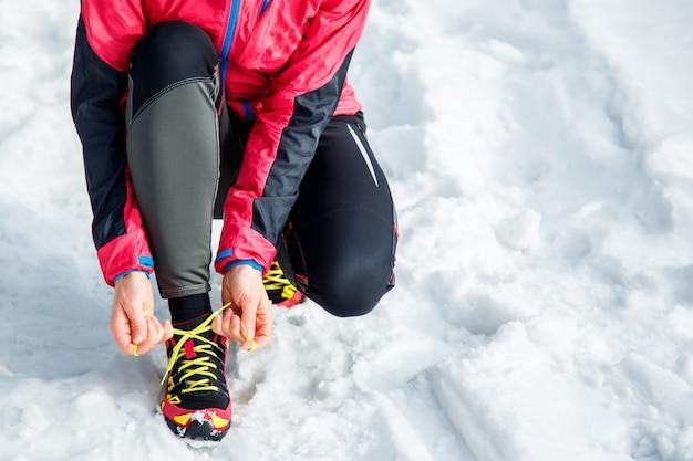 ランニングとスポーツの靴ひもを結ぶ女性。スポーティな履物をクローズアップ。フィットネスの動機と健康的なライフスタイルのコンセプト