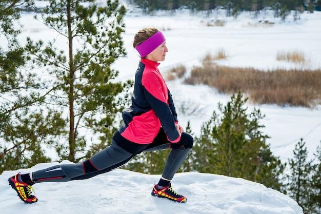 Подходит женщина делает упражнения на растяжку перед запуском на открытом воздухе. зимняя уличная тренировка