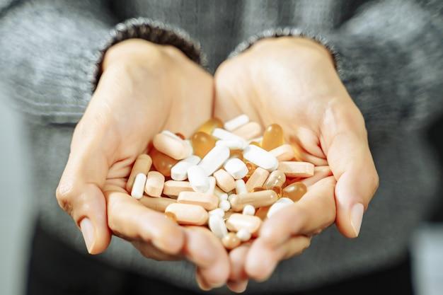 多くの異なる錠剤やカプセルを保持している女性の手のクローズアップ