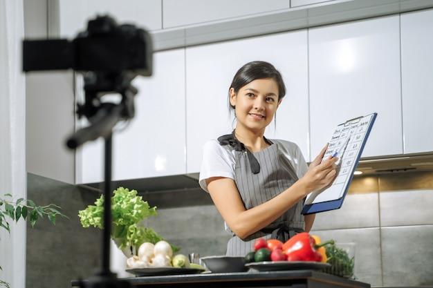 若い笑顔の女性栄養士がカロリー食品の比較表を示し、キッチンのカメラでビデオを録画します。