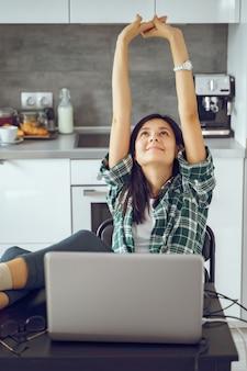 Молодая счастливая женщина протягивая и ослабляя пока работающ на компьтер-книжке в кухне дома. дистанционная работа или онлайн-обучение