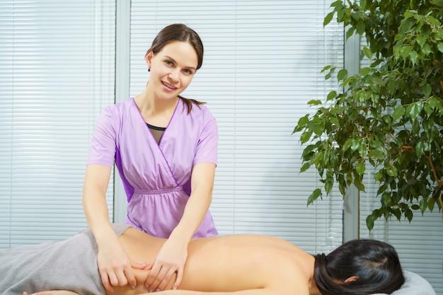 医療センターで若いブルネットをマッサージ笑顔のマッサージセラピストの女性の肖像画。