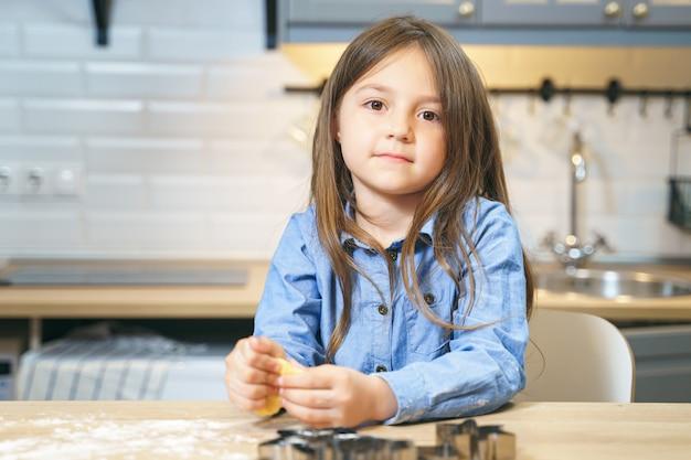 キッチンでクッキー生地を準備するかわいい笑顔の女の子の肖像画。リトルヘルパー