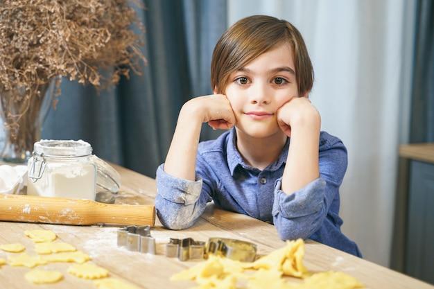 キッチンで自家製クッキーを調理するかわいい男の子の肖像画