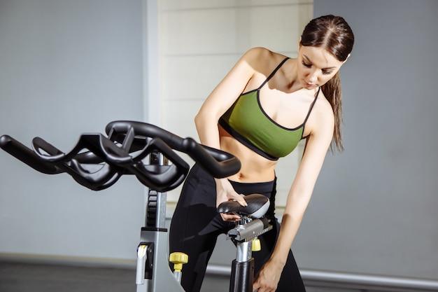 若くてきれいな女性、ジムでのトレーニングのための自転車の準備