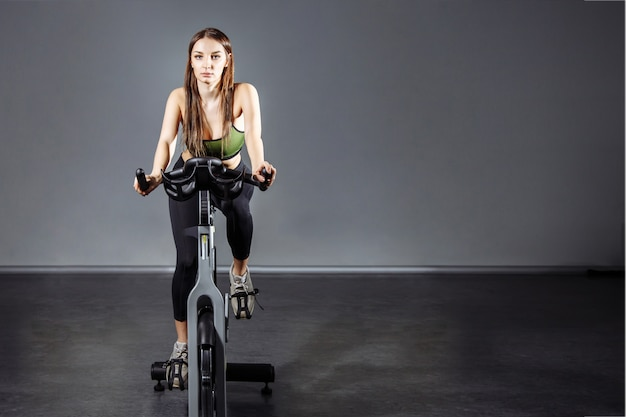 若い女性がジムでエアロバイクでエクササイズします。