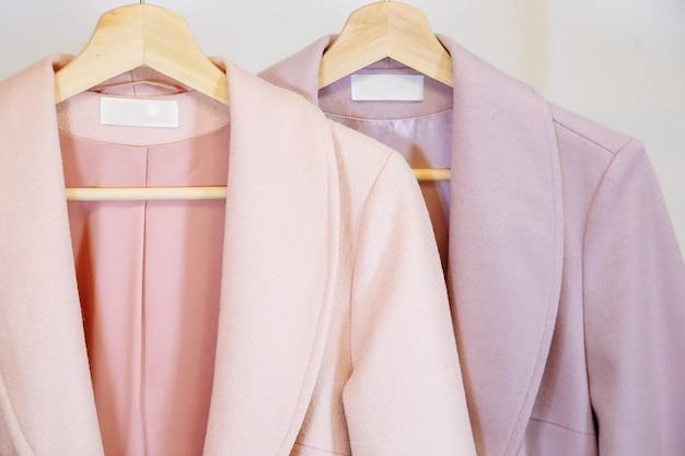 Модные осенние пальто на деревянной вешалке.