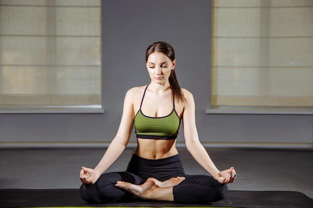 瞑想しながら蓮華座の床に座っていた若い女性