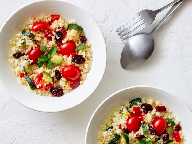 トマト、ピーマン、ズッキーニ、クランベリーのクスクスサラダ。ベジタリアンフード。ダイエット。健康的な食事。