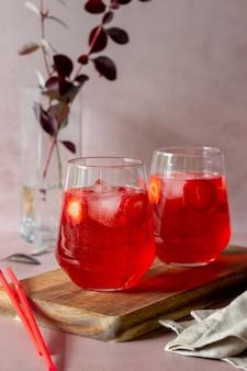 ピンクの背景にイチゴのレモネード。冷たい飲み物。夏。レシピ。