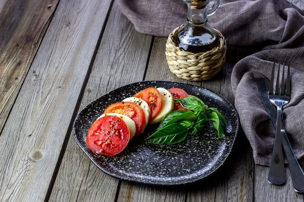 Итальянский салат с моцареллой и помидорами. деревянный. здоровая пища.