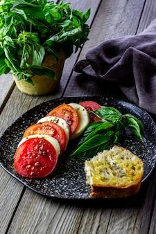 モッツァレラチーズとトマトのイタリア風カプレーゼサラダ。木製。健康食品。