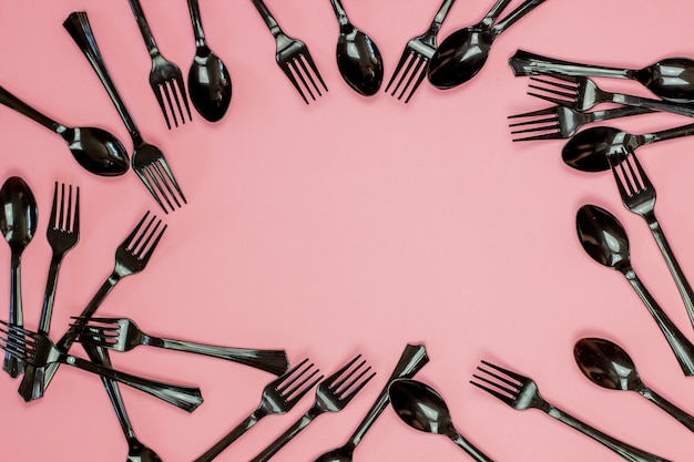 ピンクの背景にフォークとスプーン。最小限のコンセプト。プラスチックなし。