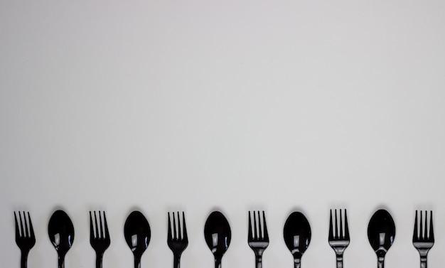 白い背景の上のフォークとスプーン。最小限のコンセプト。プラスチックなし。