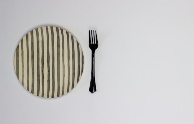白い背景の上の皿とフォーク。ミニマリズム。