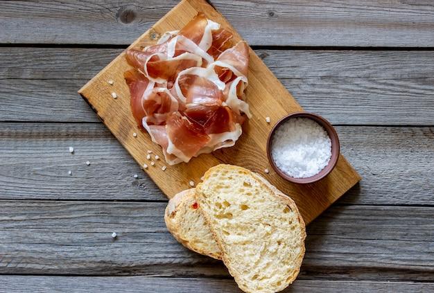 Ветчина прошутто и хлеб по дереву