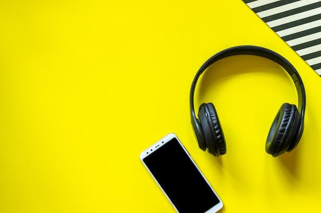黒いヘッドフォンと黄色の背景に電話。最小限のコンセプト。設計。平干し。