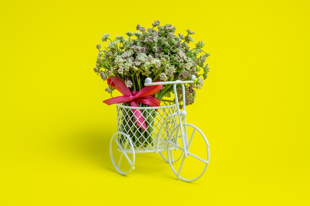Игрушечный велосипед несет цветы. идея для открытки. желтый минимализм.