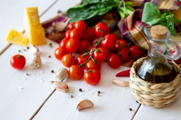 パルメザンチーズ、トマト、オリーブオイル、その他のサラダドレッシングの材料。白色の背景。