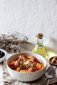 Макаронные изделия с фрикадельками и томатным соусом на деревянной предпосылке.