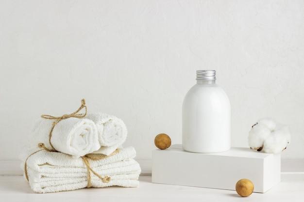 化粧品と白い背景の上のタオル。設計。最小限のコンセプト。