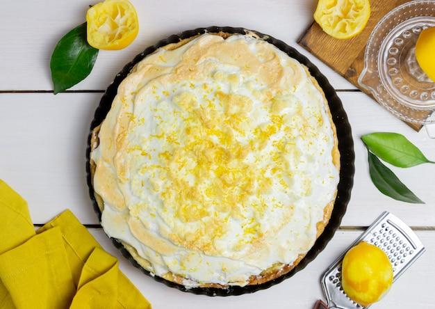 Лимонный пирог с безе на фоне деревянные.