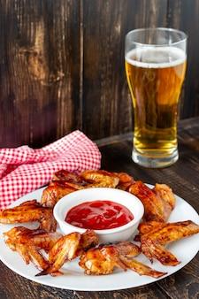 木製の背景にビールと赤いソースのグリル手羽先。ビールに軽食。バーベキュー。レシピ。