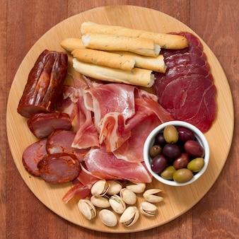 茶色の木の表面のトレイにオリーブとナッツの肉前菜