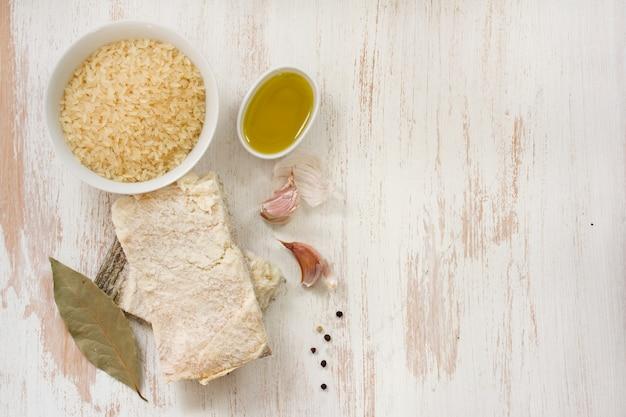 白い木製の表面に米、オリーブオイル、ニンニクとタラ