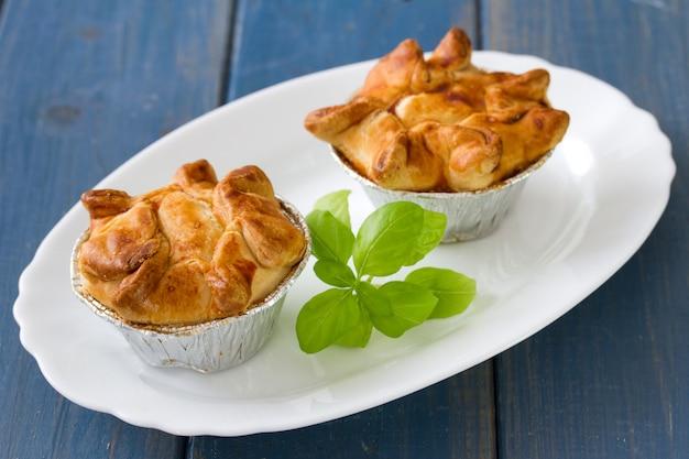 青い木製の表面に白い皿にバジルとチキンのパイ