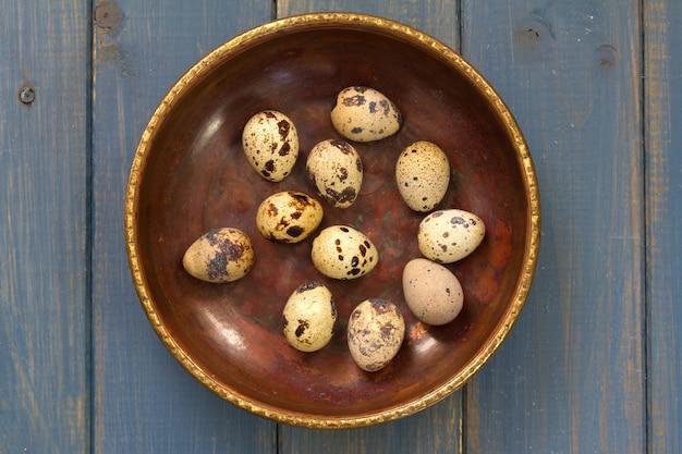 青色の背景に皿にウズラの卵