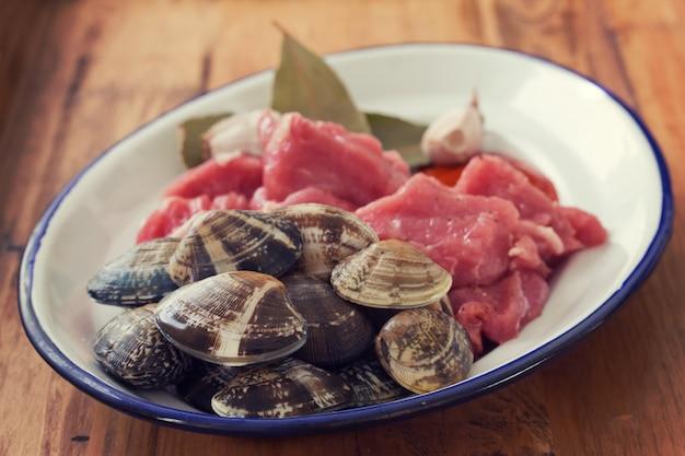 生肉にんにくと貝の茶色の木製の表面皿