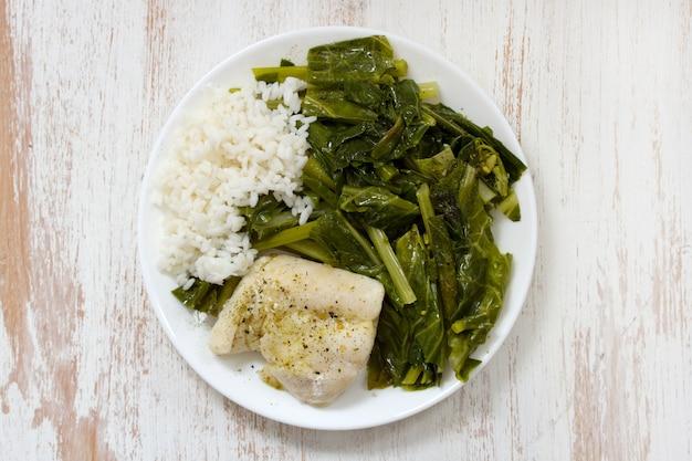 Вареная рыба с рисом и капустой на белой тарелке