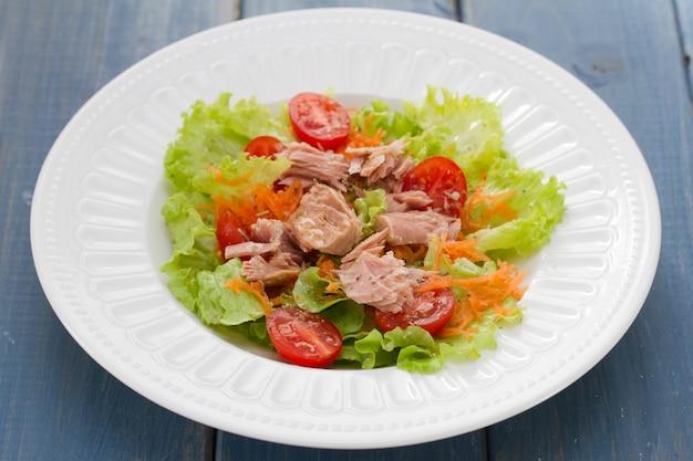 Салат из тунца на белой тарелке на синем деревянном